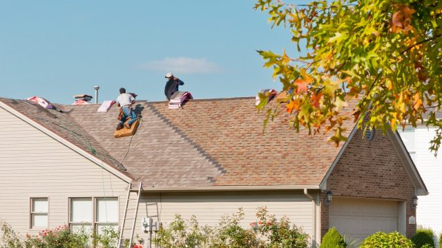 residential roofers work on a home in grosse pointe mi